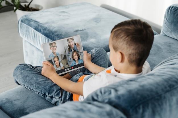 Вид сзади маленького мальчика, разговаривающего со своими друзьями через видеозвонок