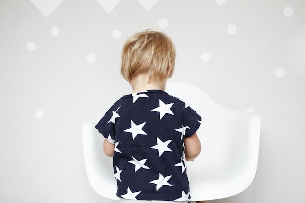 보육원에서 장난감을 가지고 노는 별과 티셔츠를 입고 금발 머리를 가진 작은 백인 소년의 다시보기. 집에서 하루를 보내고, 흰색 의자 앞에 서있는 귀여운 유아.
