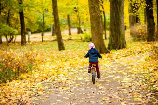 Вид сзади маленького ребенка в синем пальто, езда на велосипеде.