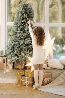 어린 소녀 docorated 크리스마스 트리의 뒷면. 큰 창의 배경