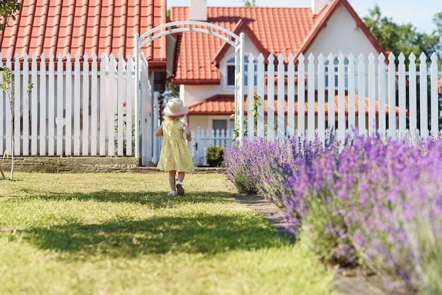 黄色の夏のドレスと麦わら帽子の少女の背面図は家の裏庭で歩く