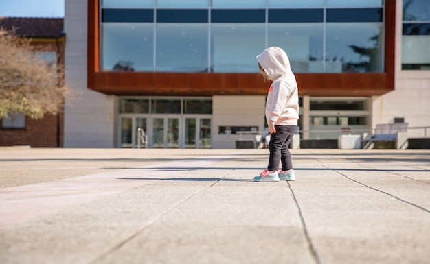 화창한 날 도시 광장에서 새 운동화를 보고 있는 후드티를 입은 어린 소녀의 뒷모습