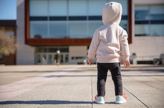 화창한 날 도시 광장에 운동화와 후드티를 입은 어린 소녀의 뒷모습
