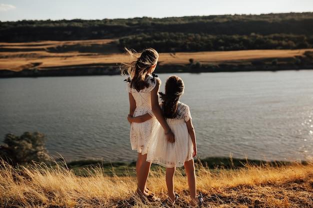Вид сзади маленьких девочек, смотрящих на реку и поля в солнечный летний день