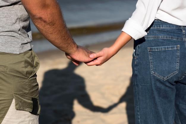 ビーチで手をつないで愛するカップルの背面図