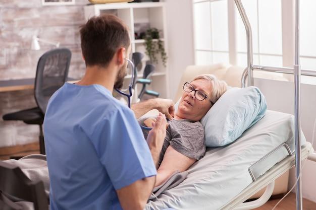 聴診器を使用してナーシングホームの女性の心臓をチェックする男性医師の背面図。