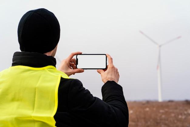 Вид сзади мужчины-инженера, фотографирующего ветряные турбины в поле