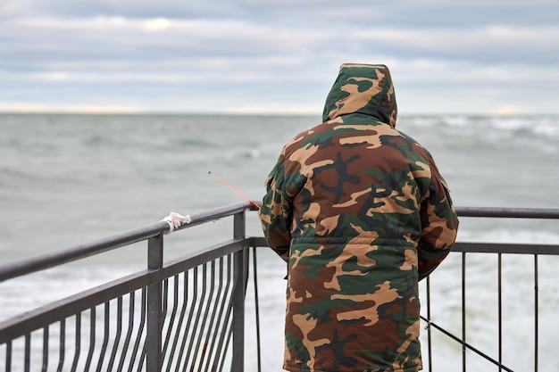 Вид сзади мужского рыбака в камуфляжном костюме, стоящего на пристани у моря и держащего удочку. красивое облачное небо, горизонт, морской пейзаж.