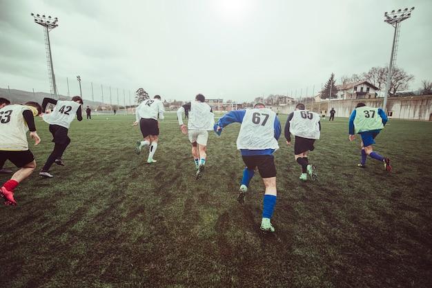 トレーニング中にサッカー場で走っている男性のサッカー選手チームの背面図。彼らは背中に白い番号のバケツを着ています。彼らは一生懸命走っています。