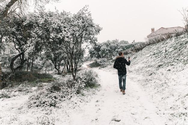 Вид сзади мужчины в верхней одежде, стоящего в заснеженном зимнем лесу и обменивающегося сообщениями на смартфоне