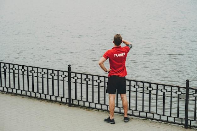 Вид сзади мужчины в красной спортивной рубашке и шортах, стоящего на набережной и смотрящего вдаль на поверхность воды, положив руку на лоб