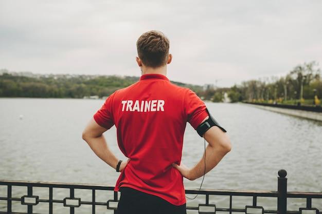 Вид сзади мужчины в спортивной одежде и красной рубашке с буквами тренера с футляром на руке, стоящего с руками на бедрах у забора у воды с облачным небом