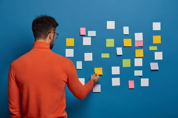 男性のプロの作品の背面図は、彼のアイデアをスティックノートに置き、ビジネスプランを作成するための主要な情報を書きます