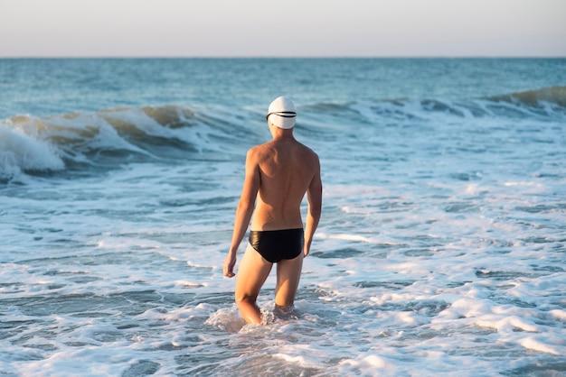 海でポーズをとって男性スイマーの背面図