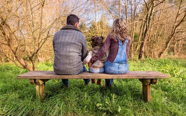 공원에 있는 나무 벤치 중앙에 앉아 있는 어린 소녀를 안고 있는 남녀의 뒷모습. 가족 레저 야외 개념입니다.