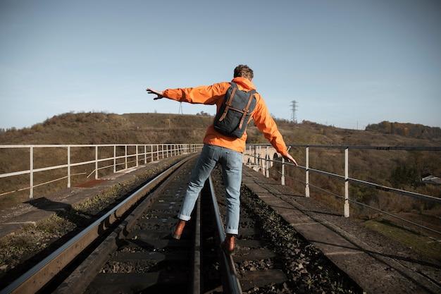 ロードトリップ中に鉄道でバランスをとる男の背面図