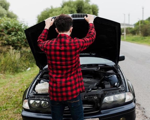 エンジンをチェックする男の背面図 無料写真