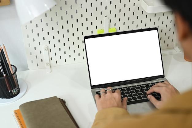 Вид сзади человек-фрилансер, работающий онлайн с портативным компьютером на домашнем офисном столе.