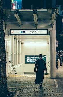 地下鉄の駅に向かっている男の背面図