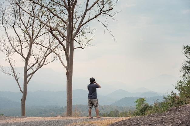 木と曇った青い空と山脈の背景とカメラを保持している男の背面図。