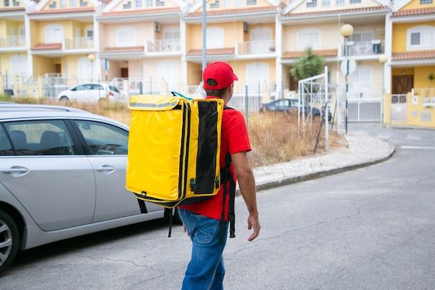 노란색 열 가방을 들고 빨간 모자에있는 남자의 다시보기. 배달원은 게시물에서 일하고 도보로 주문을 배달합니다.