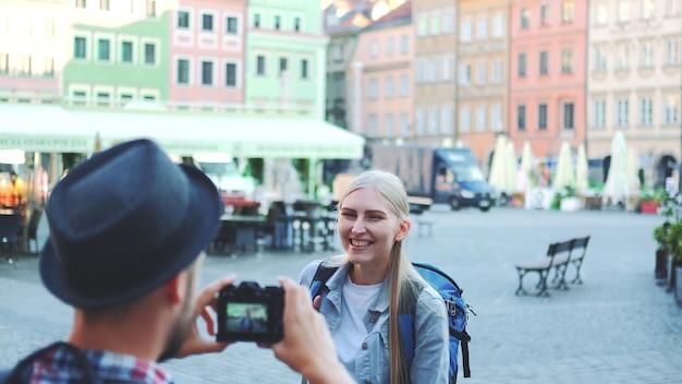 Вид сзади мужчины, фотографирующего туристку на фоне рыночной площади города