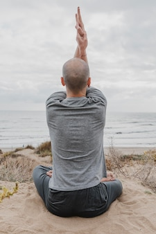 Вид сзади человека за пределами медитации во время занятий йогой