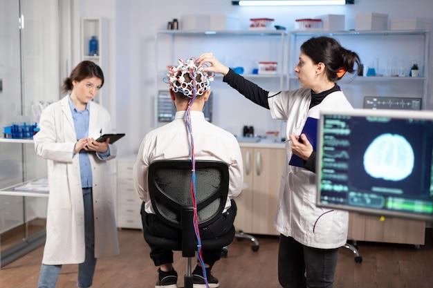 医学研究者がそれを調整し、タブレットで神経系のタイピングを調べている間、神経学研究所に座っている高性能脳波スキャンヘッドセットを身に着けている男性患者の背面図。