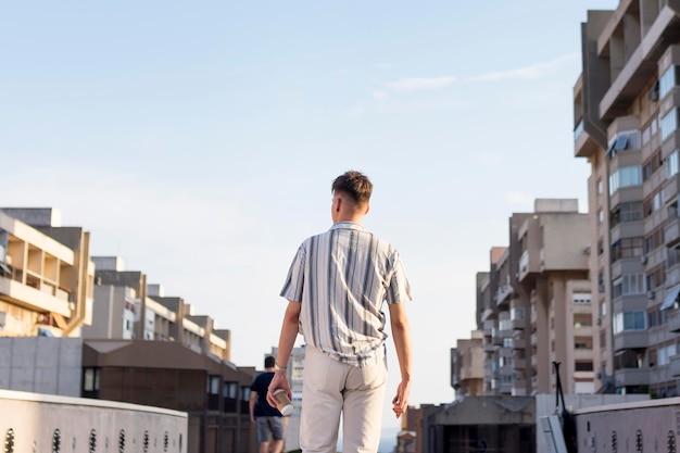 Вид сзади человека, позирующего на открытом воздухе в городе