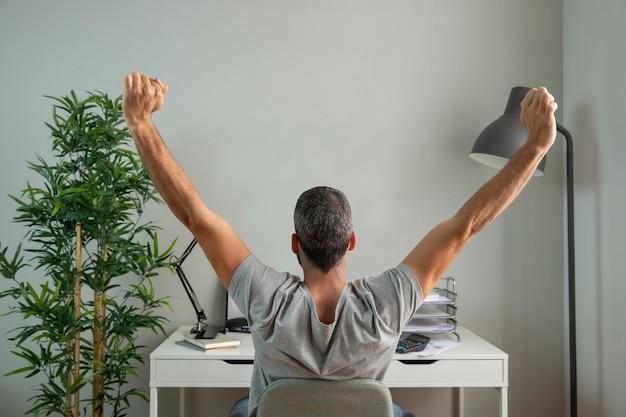 自宅で仕事をしながら腕を伸ばしている男の背面図