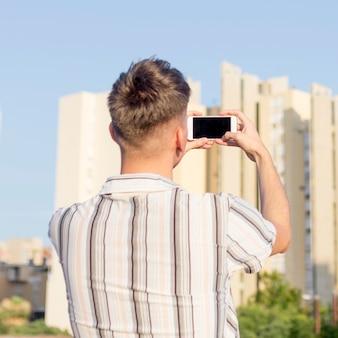 スマートフォンで屋外で写真を撮る人の背面図