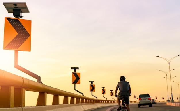 남자의 뒷모습은 자동차 뒤의 곡선 도로에서 자전거를 타는 헬멧을 착용합니다. 도로에서 안전 운전