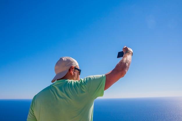 Вид сзади человека веб-автор принимает фото с камеры мобильного телефона