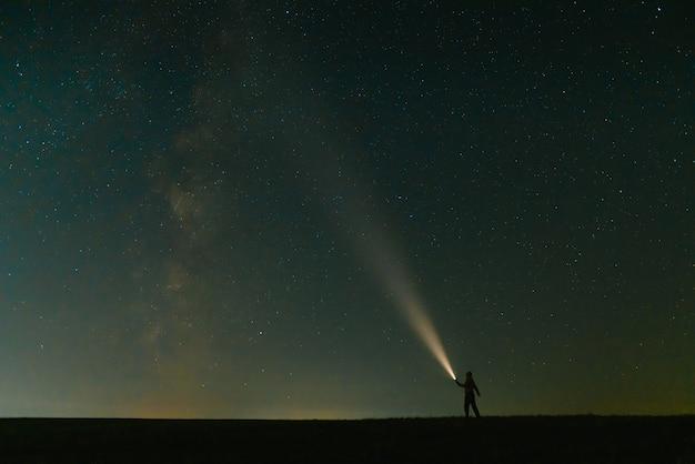美しい紺碧の星空の下で緑の芝生のフィールドに立っているヘッド懐中電灯を持つ男の背面図。