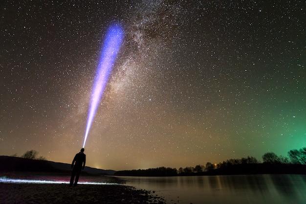 Вид сзади человека с головным фонарем, стоя на берегу реки