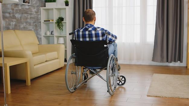 車椅子に座っている歩行障害のある男性の背面図。