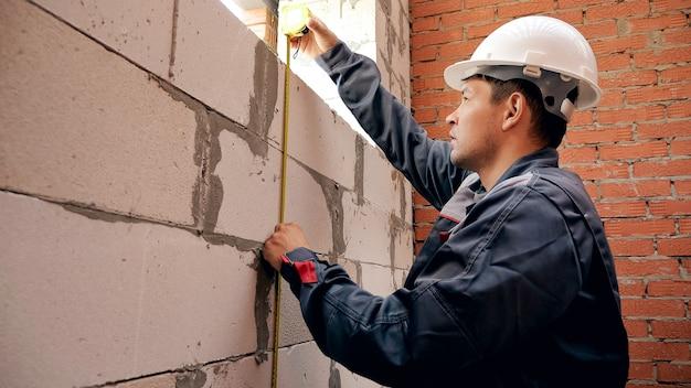 현장에서 작업하고 눈금자가 있는 벽돌 벽에 창을 측정하는 남자의 뒷모습