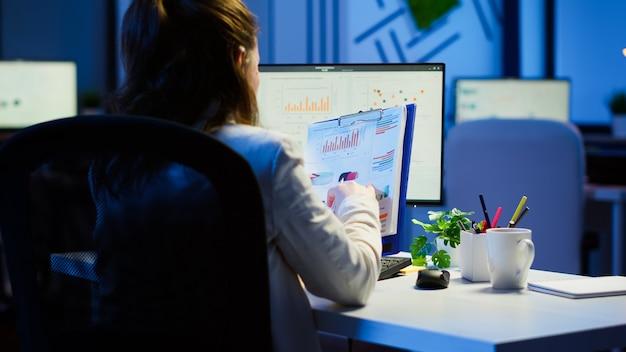 시작 비즈니스 사무실에 앉아 있는 컴퓨터 앞에서 초과 근무하는 클립보드에서 그래픽 및 재무 통계를 분석하는 관리자의 뒷모습. 현대 기술을 사용하는 바쁜 집중 직원