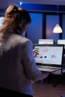 늦은 밤 과로 시작 비즈니스 사무실에 서 있는 노트북을 들고 재무 통계를 분석하는 관리자 여성의 뒷모습