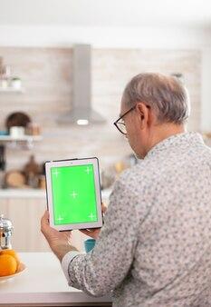 아침 식사 중에 부엌에서 크로마 키가 있는 태블릿 pc를 들고 있는 성숙한 남자의 뒷모습. 손쉬운 교체를 위해 녹색 화면 격리 모형 모형이 있는 메모장을 사용하는 정통 노인
