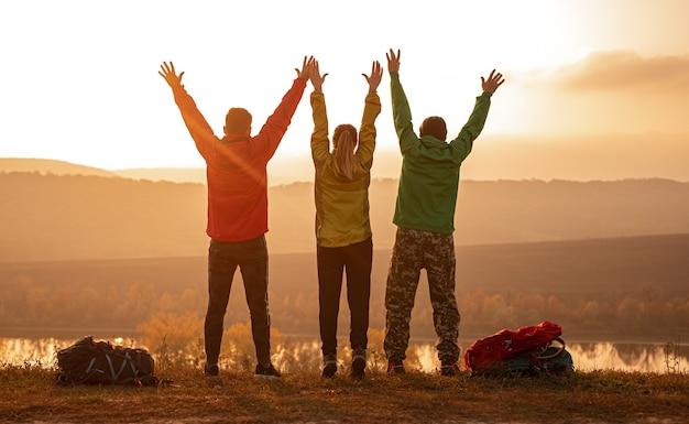週末の自然の中での旅行中に腕を上げて夕焼け空に対して自由を楽しんでいる男性と女性の背面図