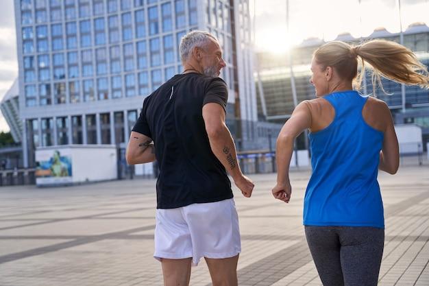 都市環境で一緒にアクティブなジョギングを続けているスポーツウェアの中年カップルの背面図