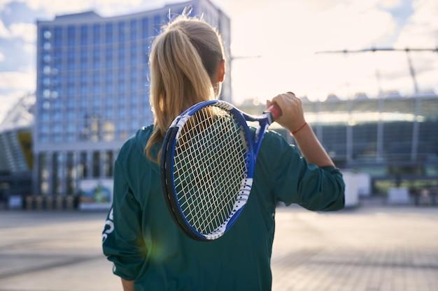 朝の準備ができて屋外に立っている中年のスポーツウーマンプロテニスプレーヤーの背面図