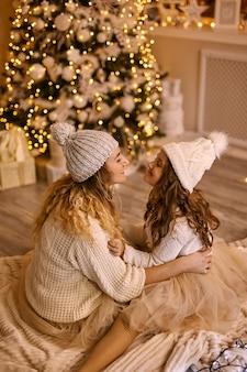 크리스마스 휴일 겨울에 빛나는 크리스마스 트리 근처에서 니트 모자를 쓴 엄마와 딸의 뒷모습