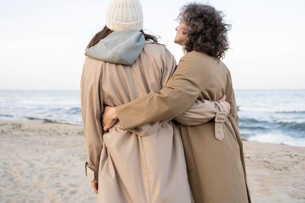 Вид сзади матери и дочери, идущей на пляже