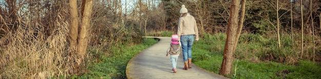 森への木製の小道を渡って手をつないで一緒に歩いている母と娘の背面図