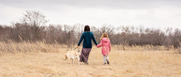 Вид сзади матери и дочери с собакой