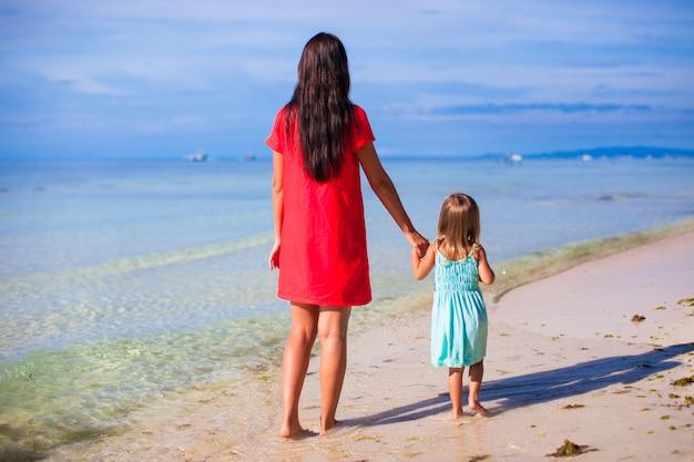 Вид сзади матери и ее маленькой дочери, глядя на море