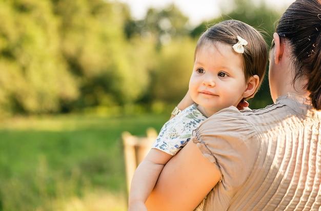 Вид сзади матери, держащей счастливую девочку на руках на фоне природы