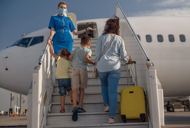 2人の小さな子供と飛行機に搭乗するスーツケースを持つ母親の背面図。家族を迎える保護マスクを着用したスチュワーデス。人、旅行、休暇の概念